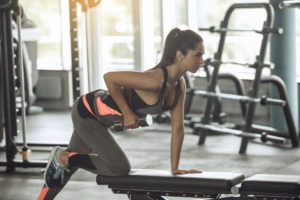 a woman exercising on a weight bench