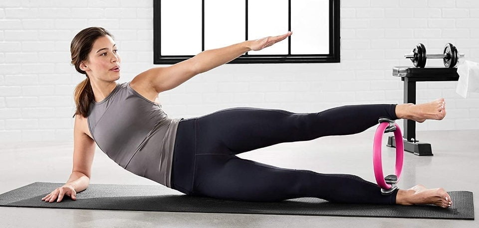 a woman exercising with a pilates ring in her house