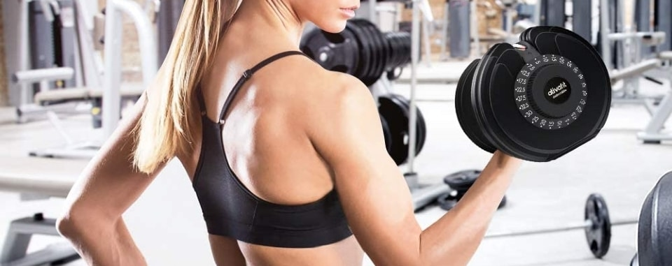 a woman exercising with an adjustable dumbbell in the gym