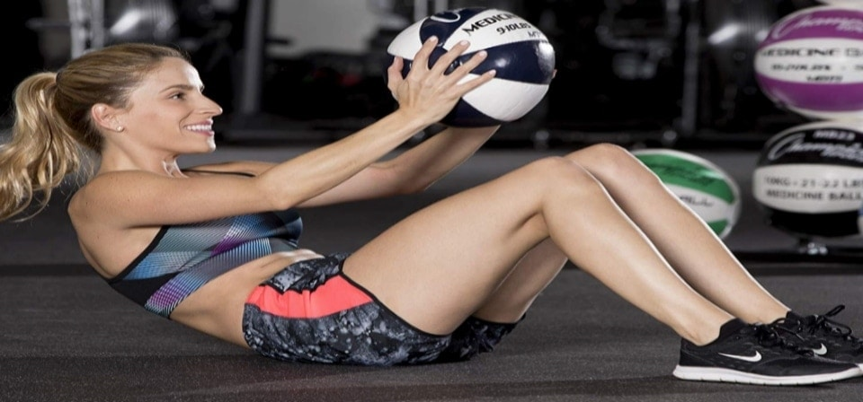 a woman holding a medicine ball in her hands