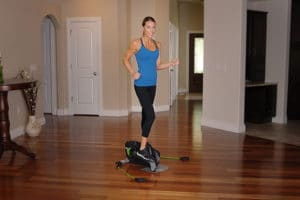a woman is exercising with an elliptical in the living room