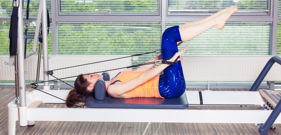 a woman is using pilates reformer