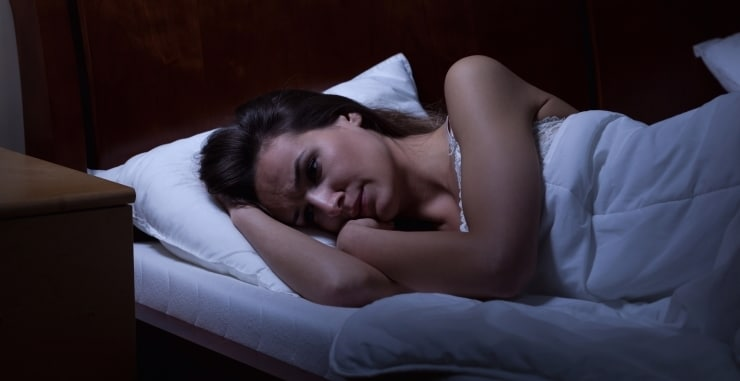 a woman lying in her bed trying to sleep