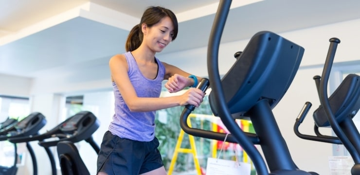a woman measuring the calories she burns with an elliptical machine