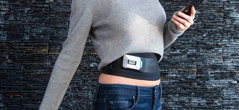 a woman sees her cell phone while using ab toning belt