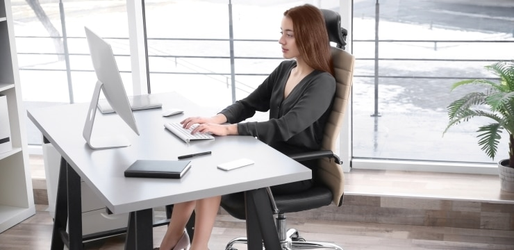 a woman sitting in front of the computer with a correct posture