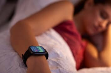 a woman sleeping with a fitness tracker
