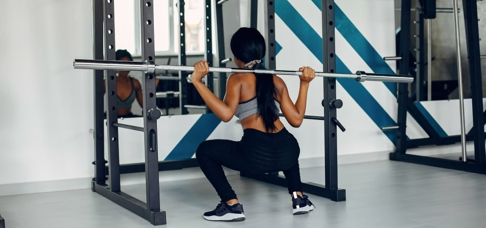 a woman squatting with a barbell in front of a mirror