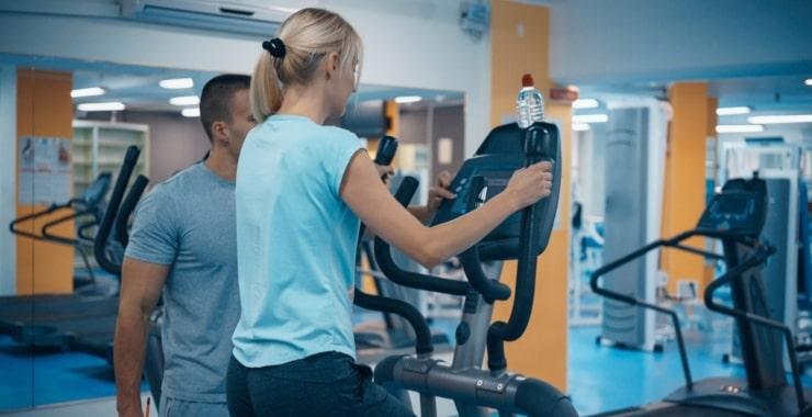 a woman using an elliptical machine at the gym