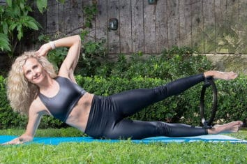 a woman using pilates ring over the grass