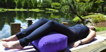 A woman lying on a yoga bolster outside by a lake