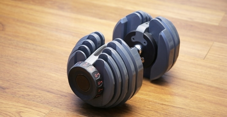 an adjustable dumbbell on a wooden floor