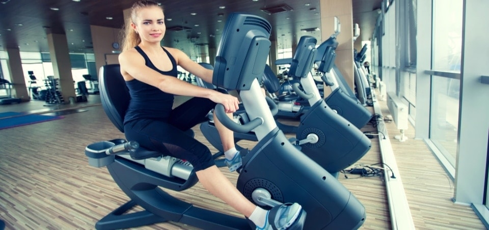 beautiful girl doing recumbent exercise bike