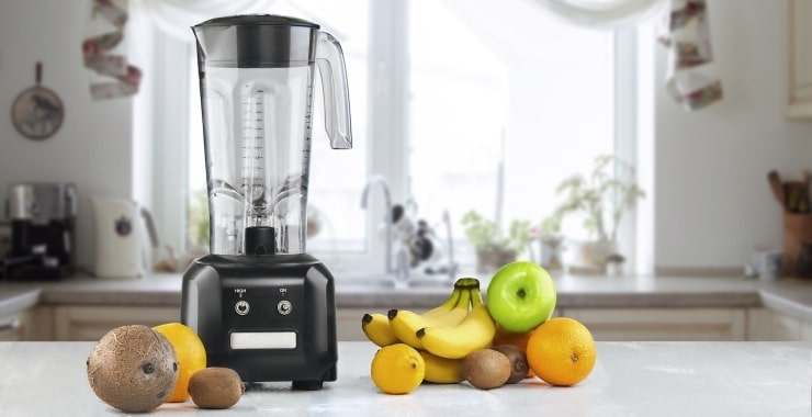 a blender and fruits on a kitchen counter