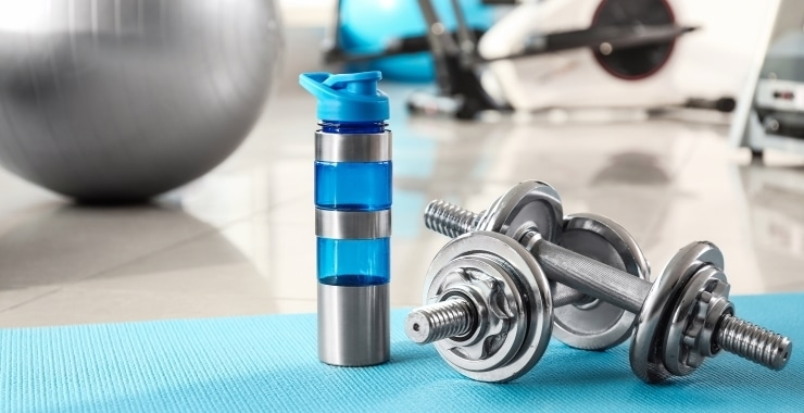 a bottle of water and adjustable dumbbells on a yoga mat in the gym