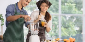 couple preparing orange juice smoothie
