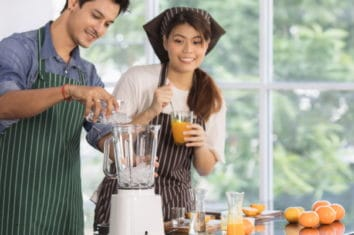 couple preparing orange juice smoothie