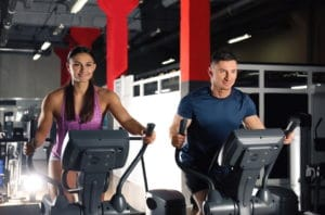 couple working out on elliptical trainers in gym