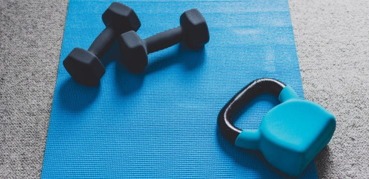 dumbbells and kettlebells on a blue mat on the floor