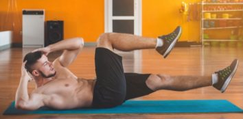 man doing sit-ups on the floor on a blue mat
