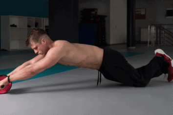 man exercising his core with an ab roller