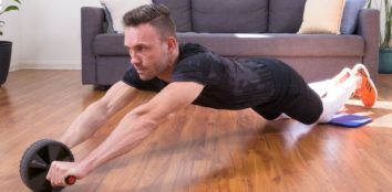 a man exercising with an ab roller on his wooden floor