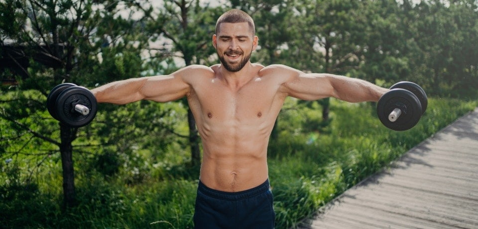 man lifting adjustable dumbbells during his outdoor workout