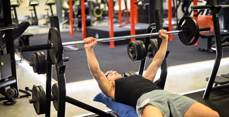 man training doing bench press in a gym