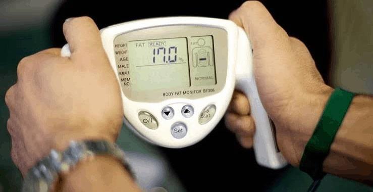 man using a body fat analyzer