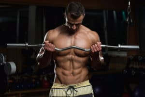 muscular man doing heavy weight exercise with a curl bar