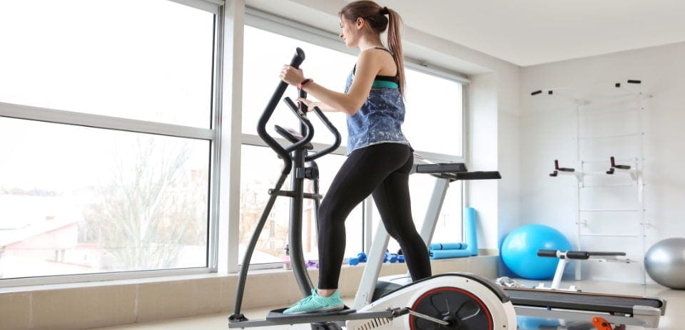 sporty young woman training on machine elliptical