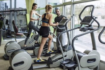 two women working out on elliptical machines