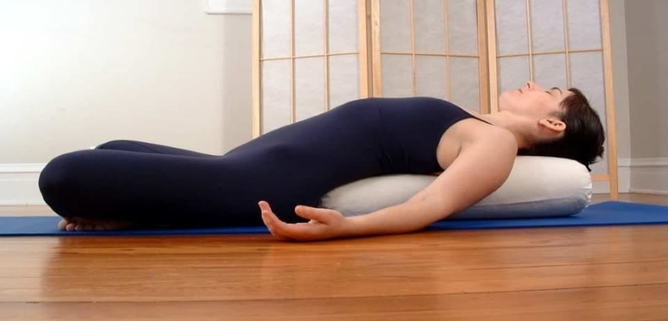underneath the woman there is a yoga bolster