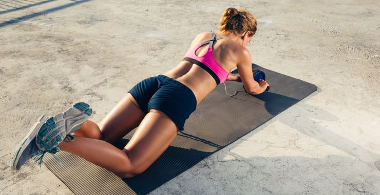 woman exercising outdoors with an ab roller