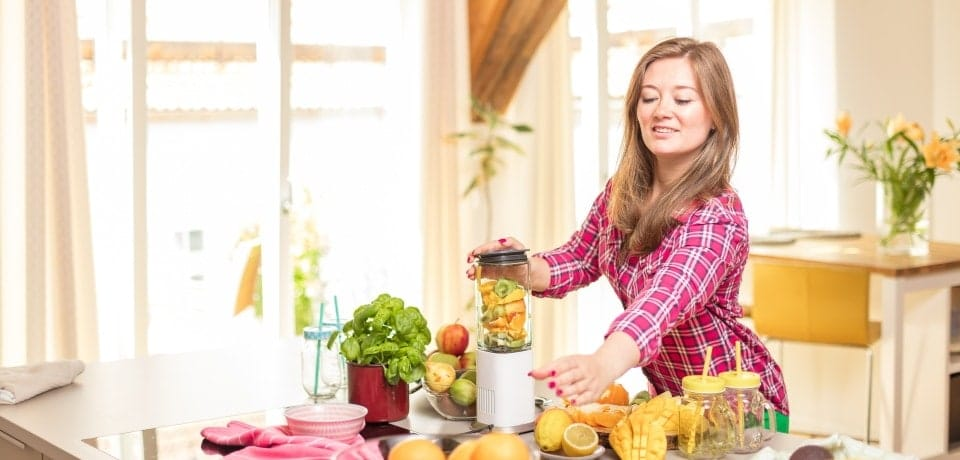 woman making smoothie with fresh vegetables in blender in kitchen at home